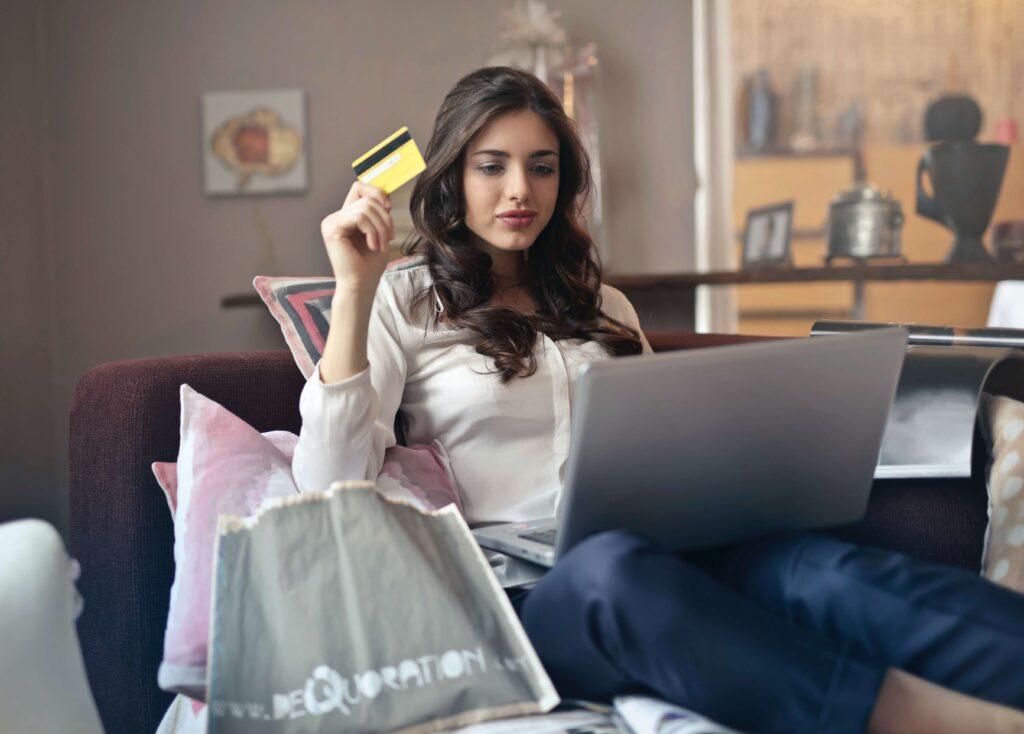 Noia comprant per internet a un ecommerce amb la targeta de crèdit a la mà